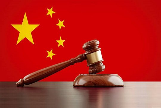Wooden gavel in front of Chinese flag. The gavel is nicely textured and it is casting soft shadows on the ground. Great use for law, justice and auction related concepts.