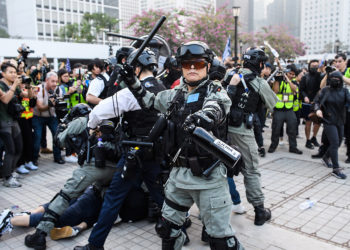A police officer holds his baton as his colleagues detain a man during a rally in Hong Kong on December 22, 2019 to show support for the Uighur minority in China. - Hong Kong riot police broke up a solidarity rally for China's Uighurs on December 22 -- with one officer drawing a pistol -- as the city's pro-democracy movement likened their plight to that of the oppressed Muslim minority. (Photo by Anthony WALLACE / AFP)