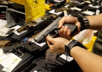 MIA01. MIAMI (EE.UU.), 13/02/2016.- Un hombre sostiene un arma Glock 19 durante la Feria de Armas de Miami hoy, sábado 13 de febrero de 2016, en Miami, Florida (Estados Unidos). La Feria de Armas de Miami, un gran arsenal expuesto al público, abre hoy sus puertas, después de que un proyecto de ley para permitir el porte de armas en universidades de Florida recibiera el primer visto bueno parlamentario. EFE/Gaston De Cardenas