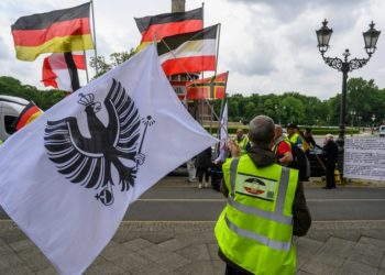 "A demonstrator waves a flag with an ""Imperial Eagle"" (Reichsadler) on it during a protest in Berlin on May 23, 2020, by right wing extremists. The group was protesting againg lockdown measures due to the new coronavirus COVID-19 pandemic. / AFP / John MACDOUGALL"