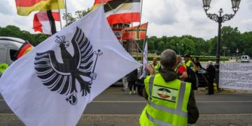 """A demonstrator waves a flag with an """"Imperial Eagle"""" (Reichsadler) on it during a protest in Berlin on May 23, 2020, by right wing extremists. The group was protesting againg lockdown measures due to the new coronavirus COVID-19 pandemic. / AFP / John MACDOUGALL"""