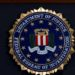 """FILE - In this June 14, 2018, file photo, the FBI seal is seen before a news conference at FBI headquarters in Washington. The FBI is grappling with a seemingly endless cycle of money laundering schemes that law enforcement officials say they're scrambling to slow through a combination of prosecution and public awareness. Beyond the run-of-the-mill plots, officials say, is a particularly concerning trend involving """"money mules."""" These are people who, unwittingly or not, use their own bank accounts to move money for criminals for purposes they think are legitimate or even noble.  (AP Photo/Jose Luis Magana, File)"""