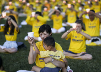 Falun Gong practitioners take part in a candlelight vigil commemorating the 20th anniversary of the persecution of Falun Gong in China, on the West Lawn of Capitol Hill on July 18, 2019. (Samira Bouaou/The Epoch Times)