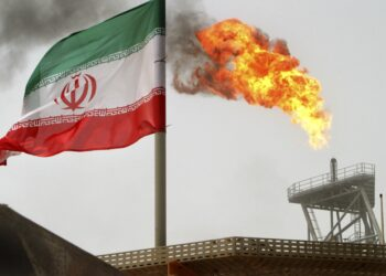 Gas flares from an oil production platform, as an Iranian flag is seen in the foreground, at the Soroush oil fields in the Persian Gulf, some 1,250 km (776 miles) south of the capital Tehran in this July 25, 2005 file photo. The United States exempted Japan and 10 EU nations from financial sanctions because they have significantly cut purchases of Iranian crude oil, but left Iran's top customers China and India exposed to the possibility of such steps. The decision announced on March 20, 2012 is a victory for the 11 countries, whose banks have been given a six-month reprieve from the threat of being cut off from the U.S. financial system under new sanctions designed to pressure Iran over its nuclear program. REUTERS/Raheb Homavandi/Files  (IRAN - Tags: ENERGY POLITICS)