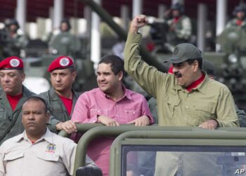 Accompanied by his son Nicolas, Venezuela's President Nicolas Maduro raises his right fist as he arrives to the military parade to commemorate the 16th anniversary of the return of the late President Hugo Chavez to power after a failed coup in 2002, in Caracas, Venezuela, Friday, April 13, 2018. (AP Photo/Ariana Cubillos)
