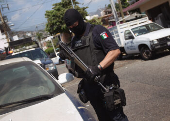 ACAPULCO, MEXICO - MARCH 01:  A Mexican federal policeman inspects an abandoned car on March 1, 2012 in Acapulco, Mexico. Stolen vehicles used by drug gangs are often found abandoned throughout the city. Drug violence surged in the coastal resort last year, making Acapulco the second most deadly city in Mexico after Juarez. One of Mexico's top tourist destinations, Acapulco has suffered a drop in business, especially from foreign tourists, due to reports of the violence. Toursim accounts for some 9 percent of Mexico's economy and about 70 percent of the output of Acapulco's state of Guerrero.  (Photo by John Moore/Getty Images)