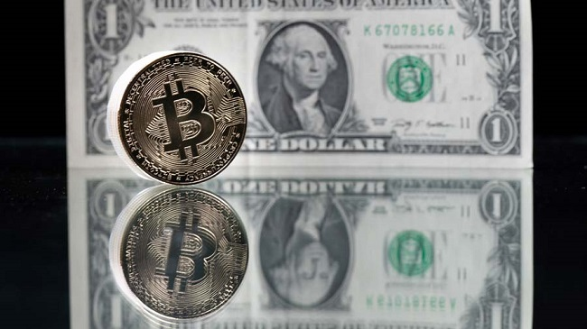This photograph taken on April 26, 2021 in Paris shows a physical imitation of the Bitcoin crypto currency pictured with a US one dollar bank note. (Photo by Martin BUREAU / AFP)